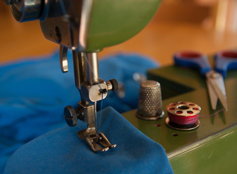 Symaskine der syr blåt stof på grøn maskine