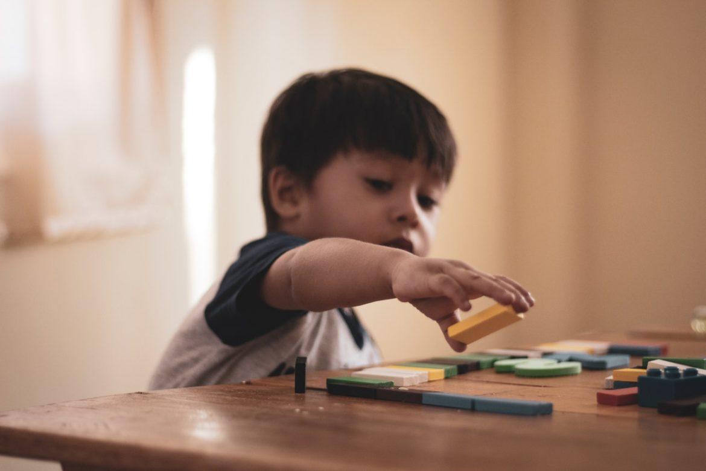 Dreng leger med klodser på bord