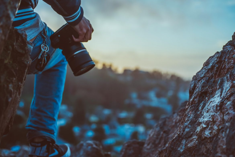 Mand er på bjerg med et kamera i hånden