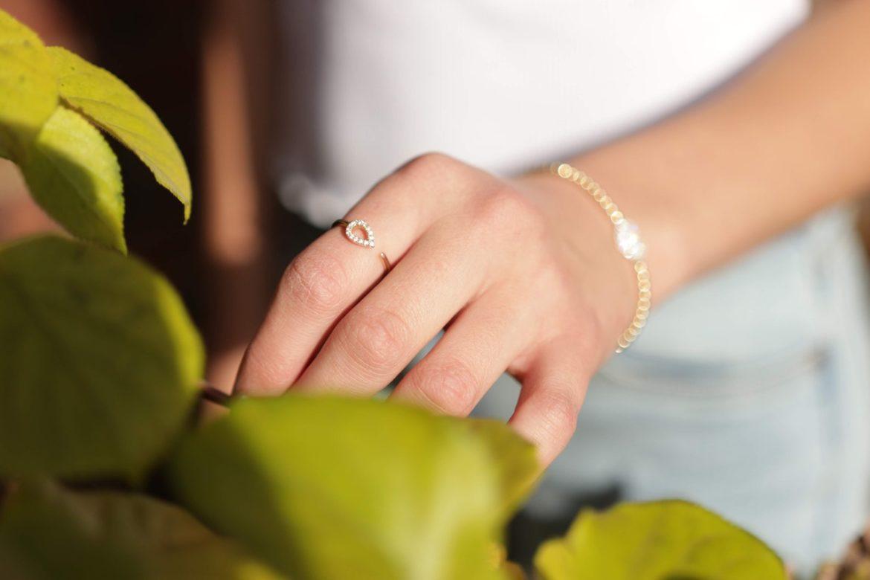 person rør ved grønne blade og har smykker på