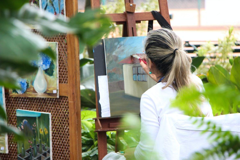 Person maler maleri udenfor blandt planter